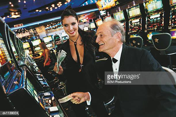 senior man inserting a us banknote into a fruit machine in front of a young woman in a casino - may december romance stock photos and pictures