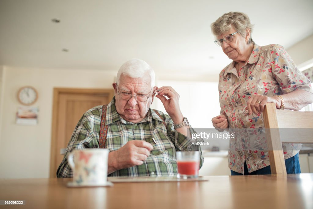 Senior Man Inserting His Hearing Aid : Stock Photo