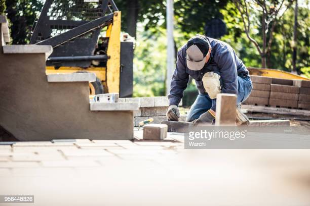 senior man installing paving stones in front of his house - paving stone stock pictures, royalty-free photos & images