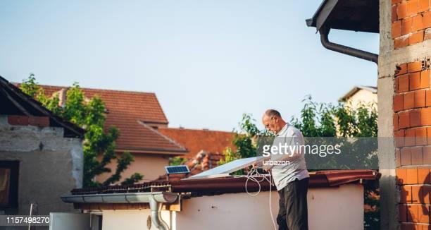 senior mann installation solarpanel - solarkraftwerk stock-fotos und bilder