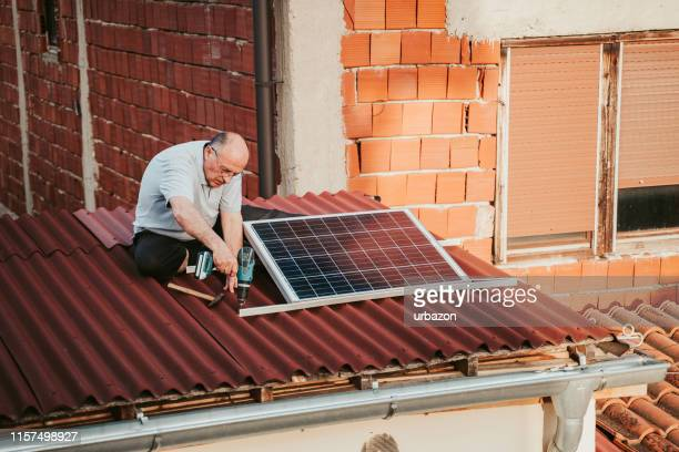 senior man installing solar panel - control panel stock pictures, royalty-free photos & images