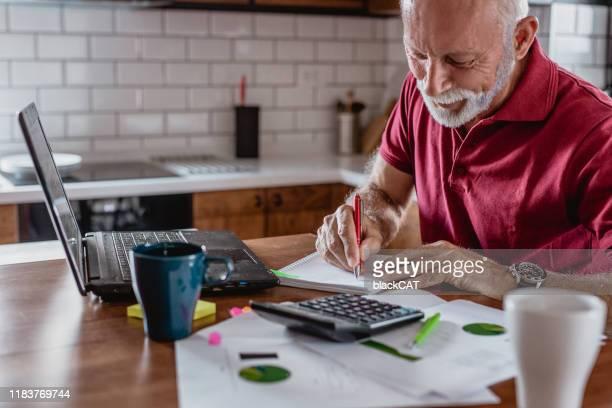 senior man is het plannen van een huis budget - pensioen thema stockfoto's en -beelden