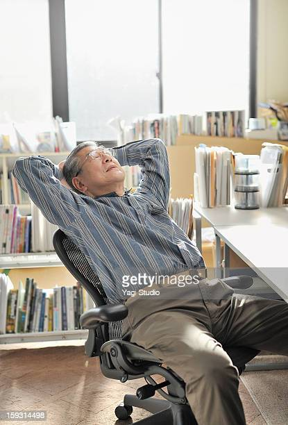 senior man is relaxing in office chair - bending over backwards stock photos and pictures