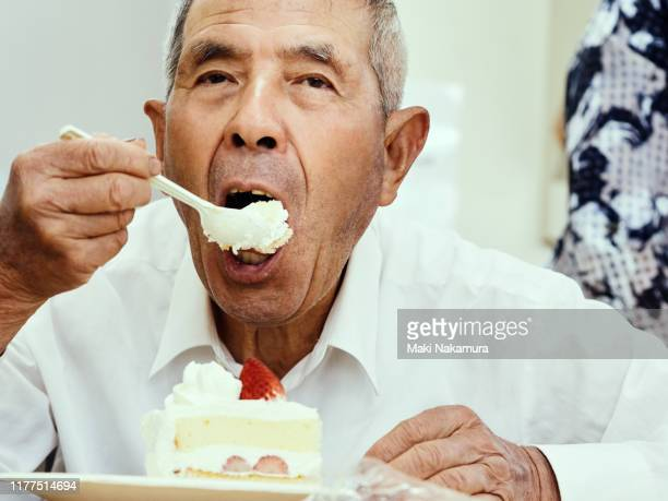 senior man is trying to eat a strawberry shortcake. - innocence stock pictures, royalty-free photos & images