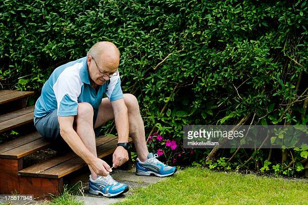 senior man is tying a sports shoe before running - tighten stock photos and pictures