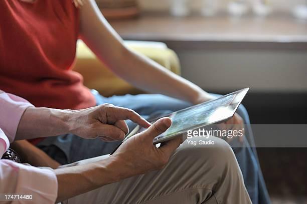 Senior man is using a digital tablet in living