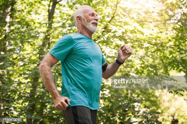 senior man jogging in the morning living healthy - 60 69 years stock pictures, royalty-free photos & images