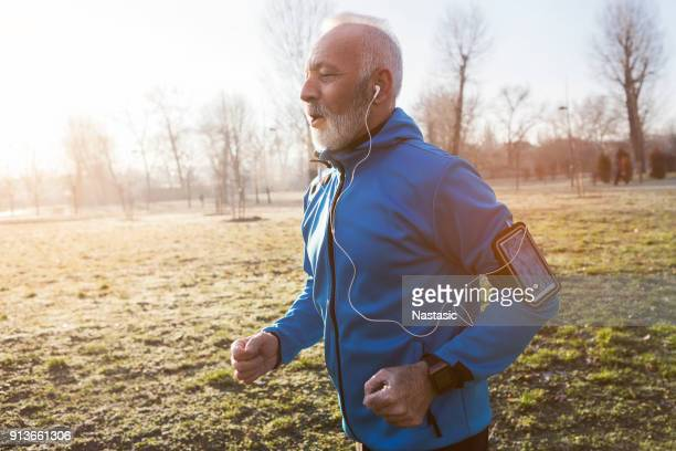 senior man jogging in the morning - 60 64 years stock pictures, royalty-free photos & images