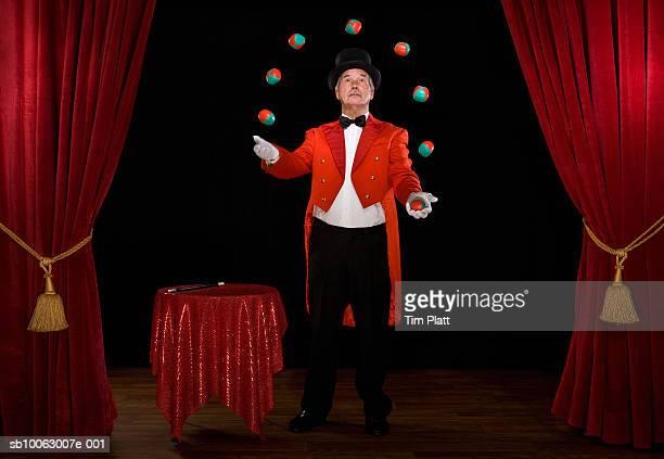 Senior man juggling balls on stage
