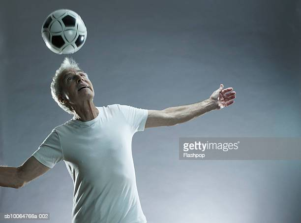 Senior man juggling football indoors