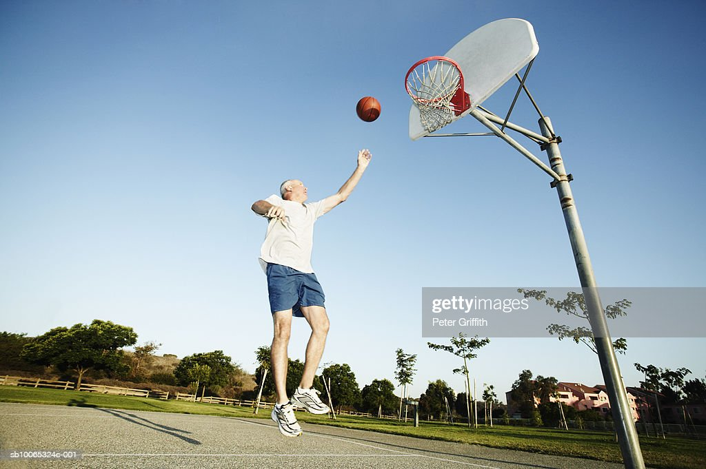 Senior man jumping for basketball on outdoor court : Foto stock