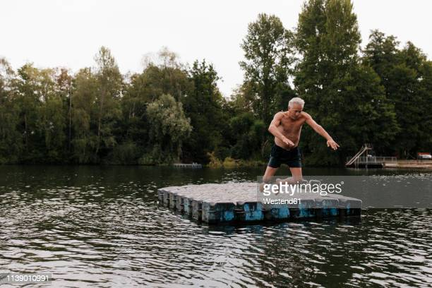 senior man jumping from raft in a lake - 気が若い ストックフォトと画像