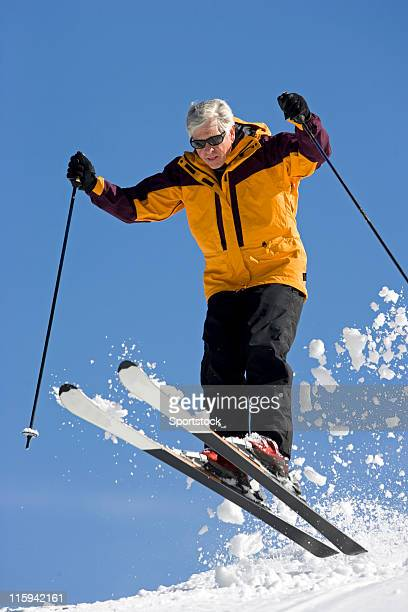 senior man jumping on snow skis - ski pole stock pictures, royalty-free photos & images