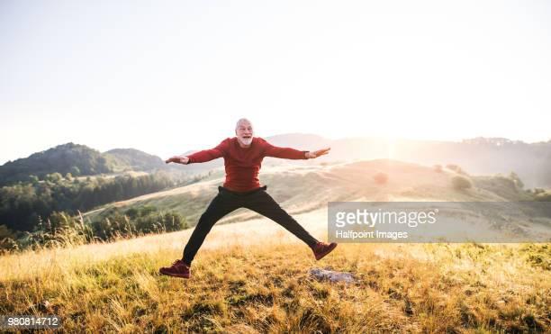 senior man jumping outdoors in nature in the foggy morning. copy space. - nur erwachsene stock-fotos und bilder
