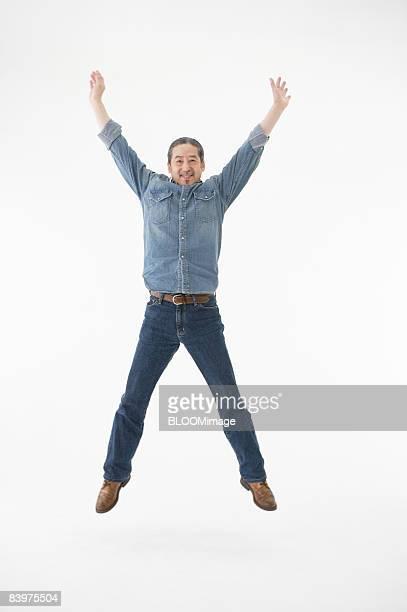 Senior man jumping, studio shot