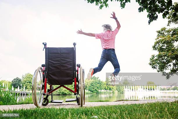 Senior man jumping up from his wheelchair