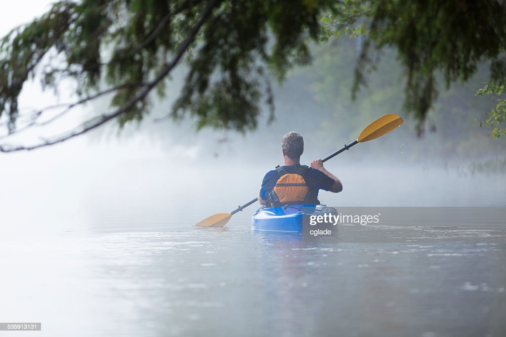 Senior man kayaking in morning mist : Stock Photo