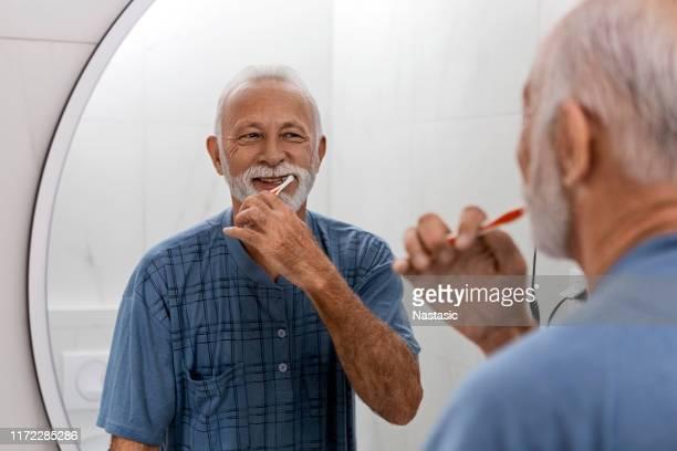 senior mann hält ihre zahnhygiene - zahnpflege stock-fotos und bilder