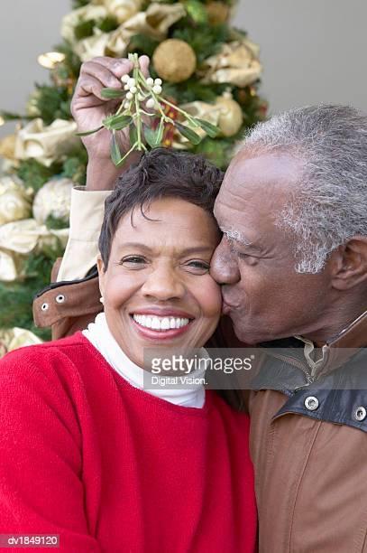Senior Man Kissing a Senior Woman Under the Mistletoe