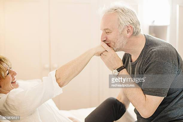 Senior man kissing mature woman's hand