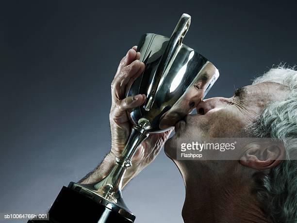 Senior man kissing trophy, profile, studio shot