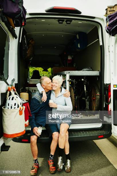 senior man kissing wife at back of camper van after mountain bike ride - heterosexual couple stock pictures, royalty-free photos & images