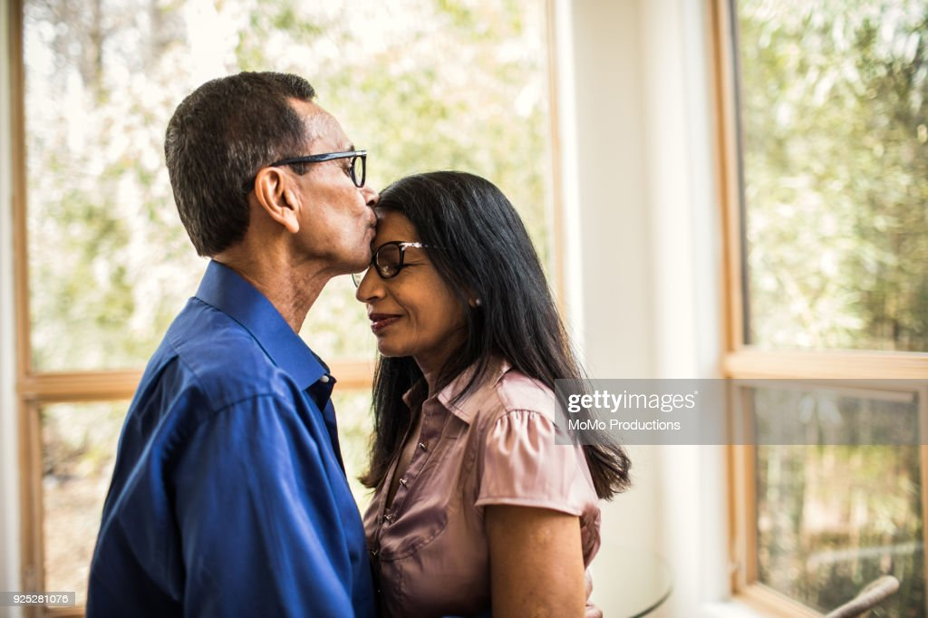 Senior man kissing wife at home : Stock Photo