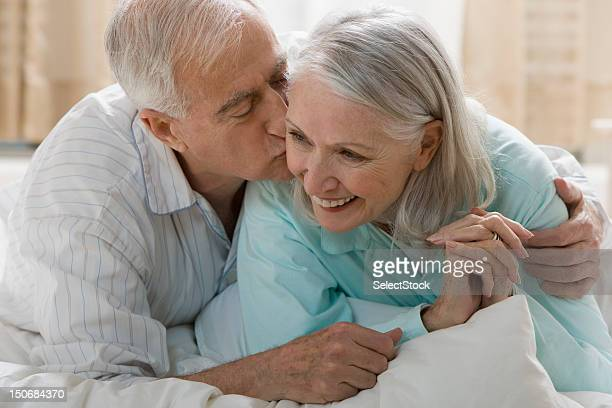 Senior man kissing wife in bed