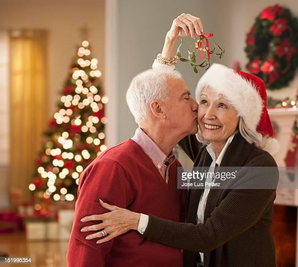 Senior man kissing wife under mistletoe