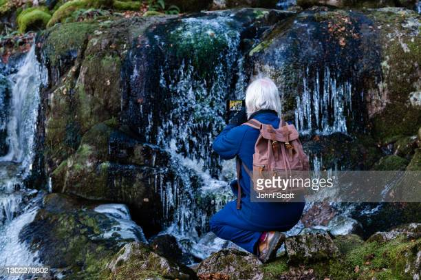 senior man kneeling down to take a photograph of a frozen waterfall - johnfscott stock pictures, royalty-free photos & images