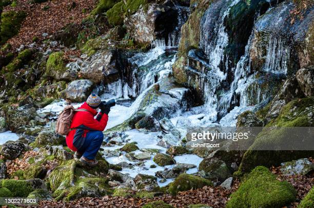 senior man kneeling to take a photograph of a frozen waterfall using a dslr - johnfscott stock pictures, royalty-free photos & images