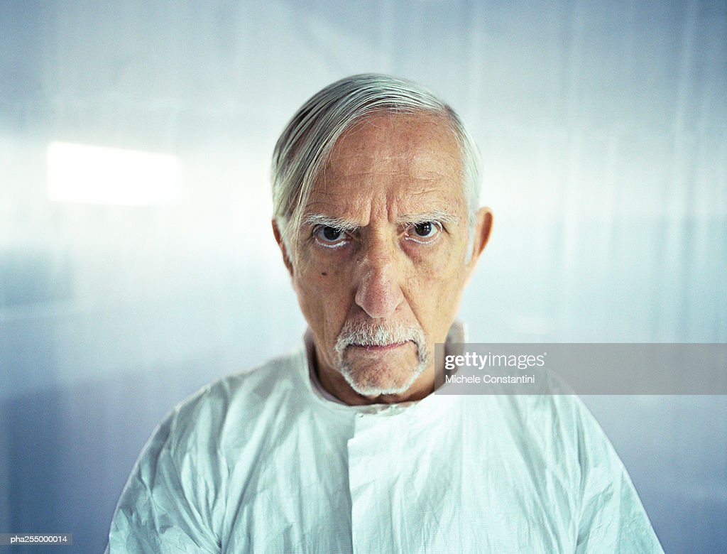 Senior man knitting brows, head and shoulders, front view : Stockfoto