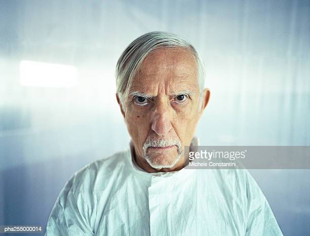 senior man knitting brows, head and shoulders, front view - cruel stock pictures, royalty-free photos & images