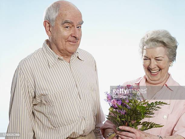 Senior man knows she's happy when he gives her flowers
