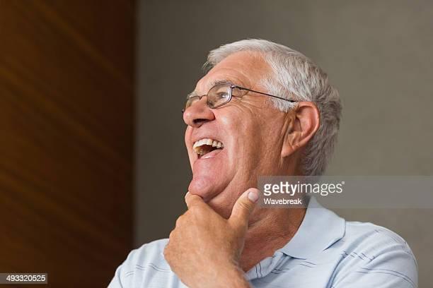 Senior man laughing gegen Grauen Wand
