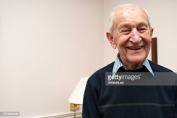 senior man laughing standing up in his living room - affectionate stock pictures, royalty-free photos & images