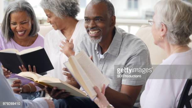 senior man leads bible study in retirement community - christianity stock pictures, royalty-free photos & images