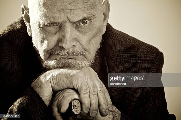 senior man leaning head on his cane, sepia toned - ebenezer scrooge stock photos and pictures