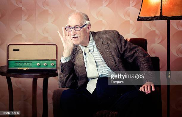 senior man leaning in to listen to retro radio - luisteren stockfoto's en -beelden