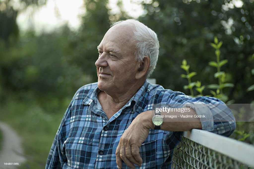 A senior man leaning on a fence and looking away serenely : Stock Photo