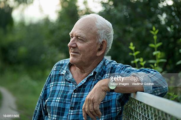 A senior man leaning on a fence and looking away serenely
