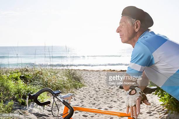 Senior man leaning on bike seat, resting.