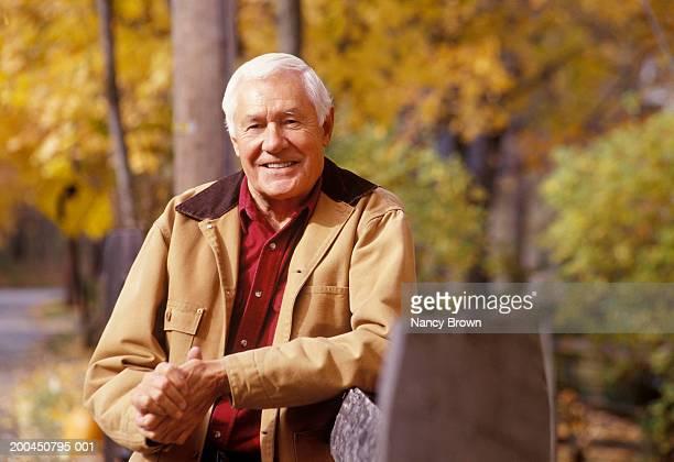 senior man leaning on fence, portrait, autumn - chaqueta fotografías e imágenes de stock