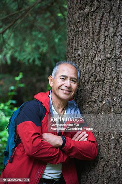 Senior man leaning on tree, portrait