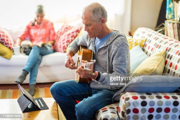 senior man learning guitar by watching online tutorial - leisure activity stock pictures, royalty-free photos & images