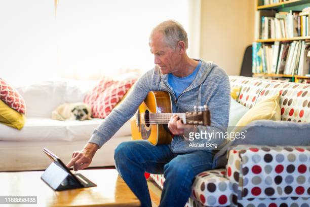 senior man learning guitar by watching online tutorial - plucking an instrument stock pictures, royalty-free photos & images