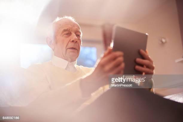 Senior man leren zijn digitale tablet gebruiken