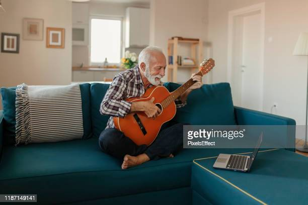 senior man learns to play acoustic guitar online - independence stock pictures, royalty-free photos & images