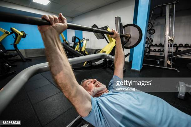 Senior man lifting bar bell in the gym with arms raised