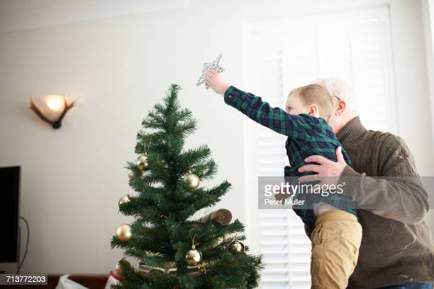senior man lifting grandson to place star on christmas tree - putting stock pictures, royalty-free photos & images